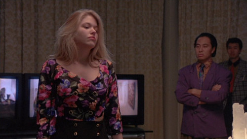 Screenshot of a blonde woman wearing a bold floral shirt, which is low-cut and double-breasted, along with a skirt which also has two rows of buttons. There's a dude in the background with a cool peach shirt and purple suit jacket.