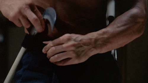 Screenshot of a shirtless man putting what may be a sickle in his belt.