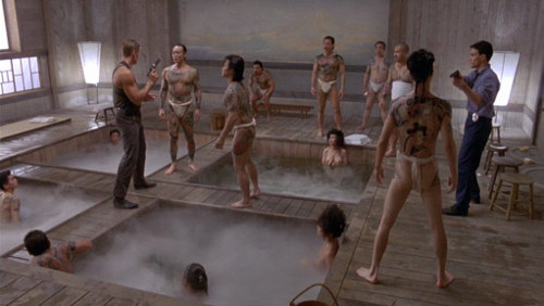 Screenshot of Lundgren and Lee confronting the gangsters in the bathhouse.