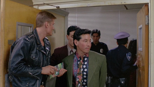 Screenshot of a guy coming into the station. He is wearing a khaki suit jacket and an amazing polka-dot and paisley shirt.
