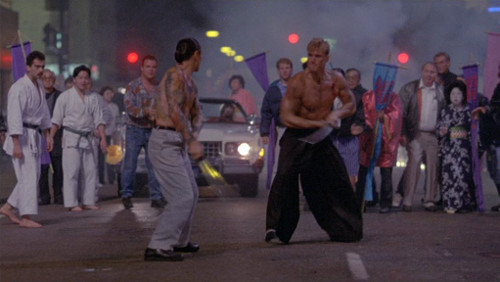 Screenshot of Lundgren and Tagawa fighting with katana, shirtless.