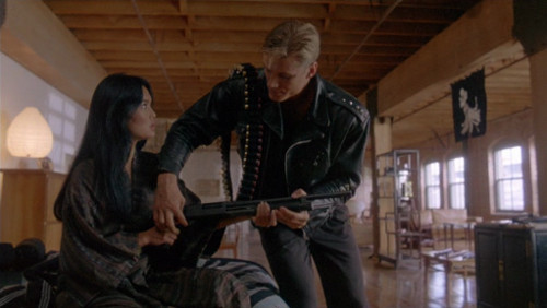 Screenshot of Lundgren showing Carrere how to use a big gun.