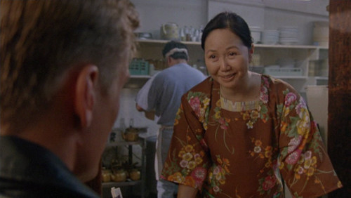 Screenshot of a smiling middle-aged Japanese woman, in a super-sweet brown floral outfit.
