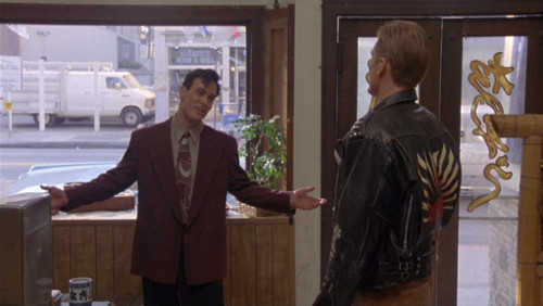 Screenshot of Lee in a superfly suit, arms open wide, and Lundgren in a leather jacket, looking dubious.
