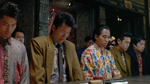 Screenshot of a row of seated gangsters, wearing amazing and colourful suits. One in particular has a different pattern on each side of the shirt, and the shirt pocket matches the pattern on the opposite side.