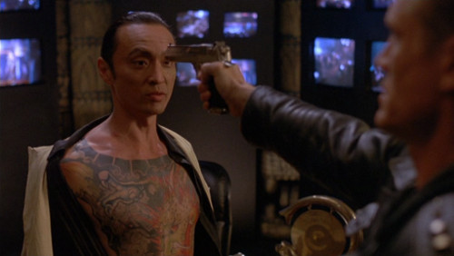 Screenshot showing Lundgren pointing the gun at the head of a guy with his shirt open; you can see said guy's impressive full-torso tattoo.