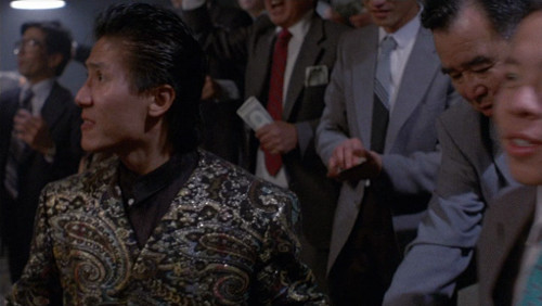 Screenshot of a dude in an amazing patterned sparkly shirt.