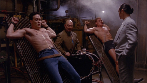 Screenshot of Lee and Lundgren, shirts off, on racks, with strange electrical devices plugged in.